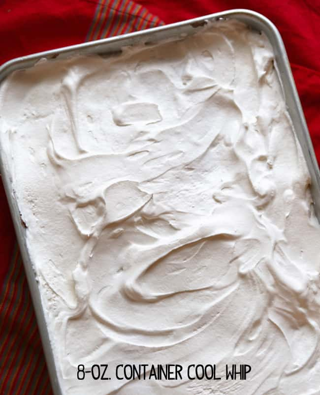 Cool Whip spread over frozen dessert in a baking pan