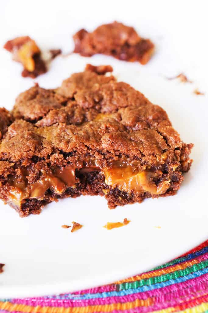 close up of a brownie with caramel oozing out of the middle