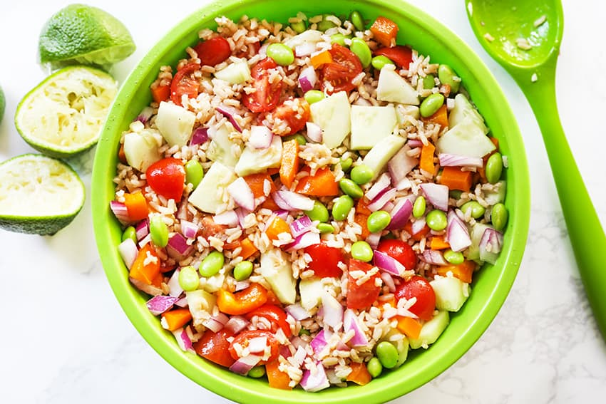 Top view of bowl of vegetable rice salad with limes nearby