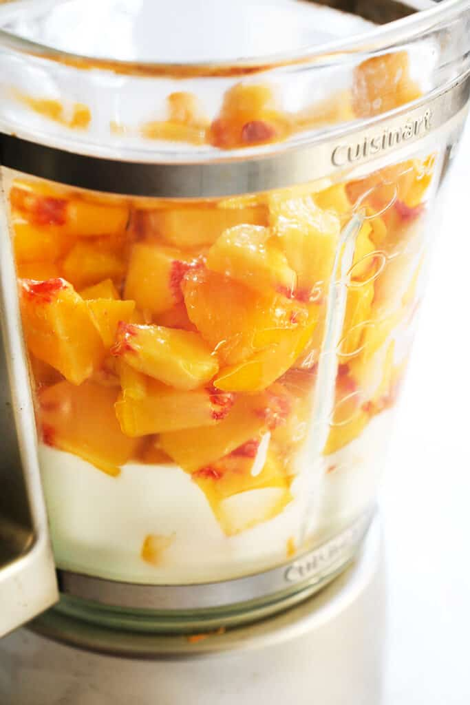 blender with chopped peaches, yogurt and honey inside