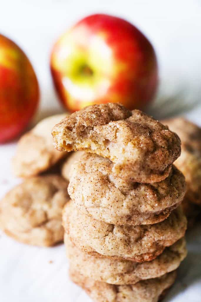 tall stack of apple snickerdoodle cookies with the top one having a bite removed