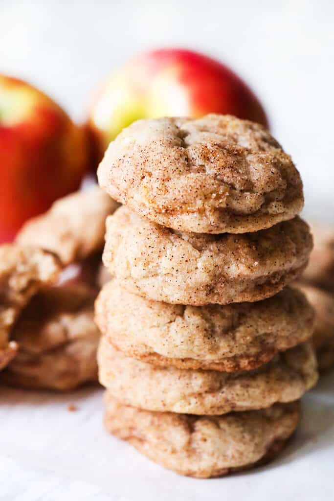 stack of apple snickerdoodle cookies with apples in background
