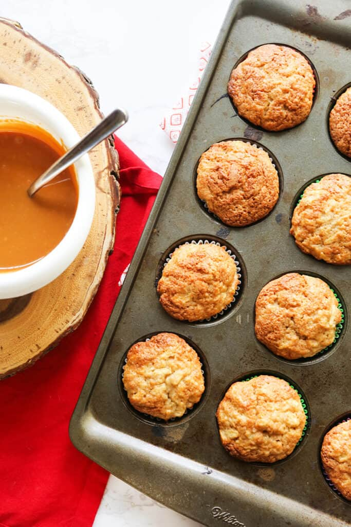 pan of cupcakes sitting next to a bowl of melted caramel