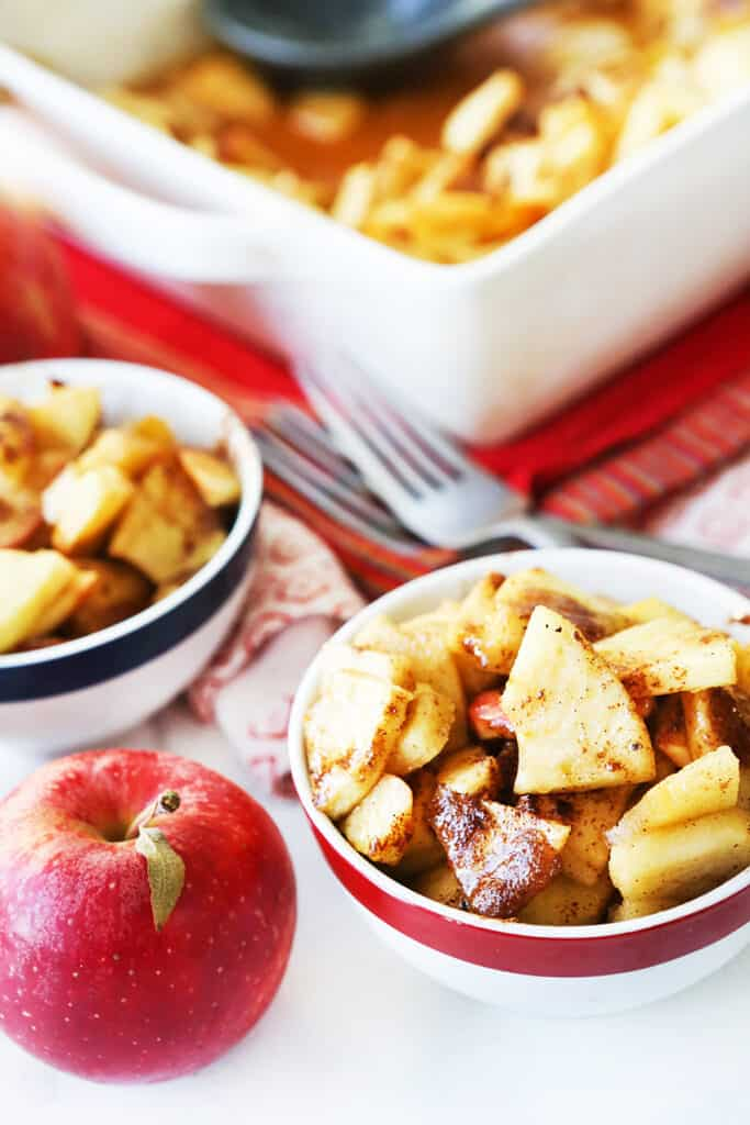 cinnamon baked apples in serving dishes next to baking pan