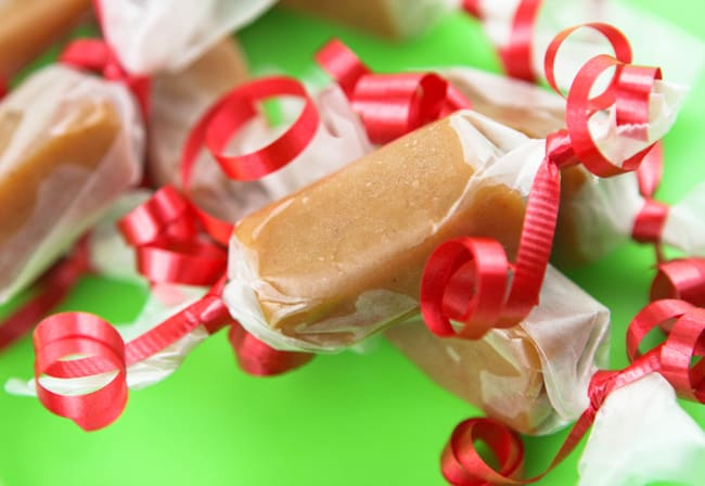homemade caramels wrapped in wax paper and tied with red ribbon