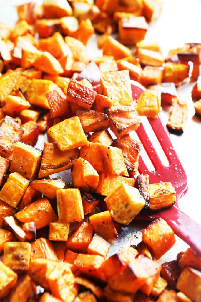 roasted sweet potatoes on parchment paper with a spatula nearby