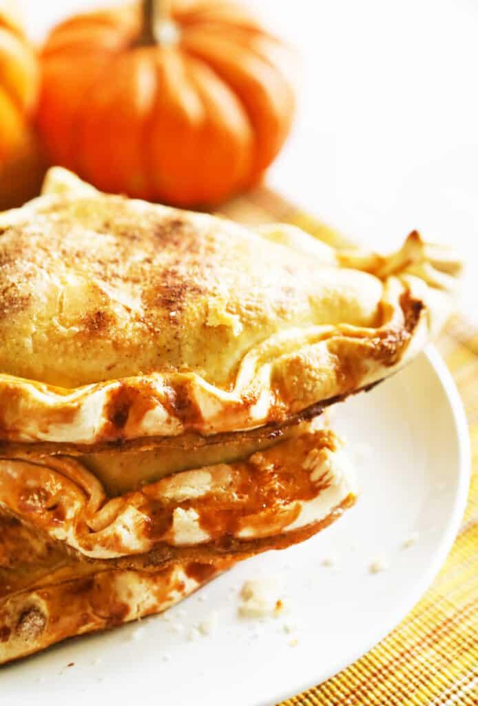 Stacked hand pies on a plate with little pumpkins in the background