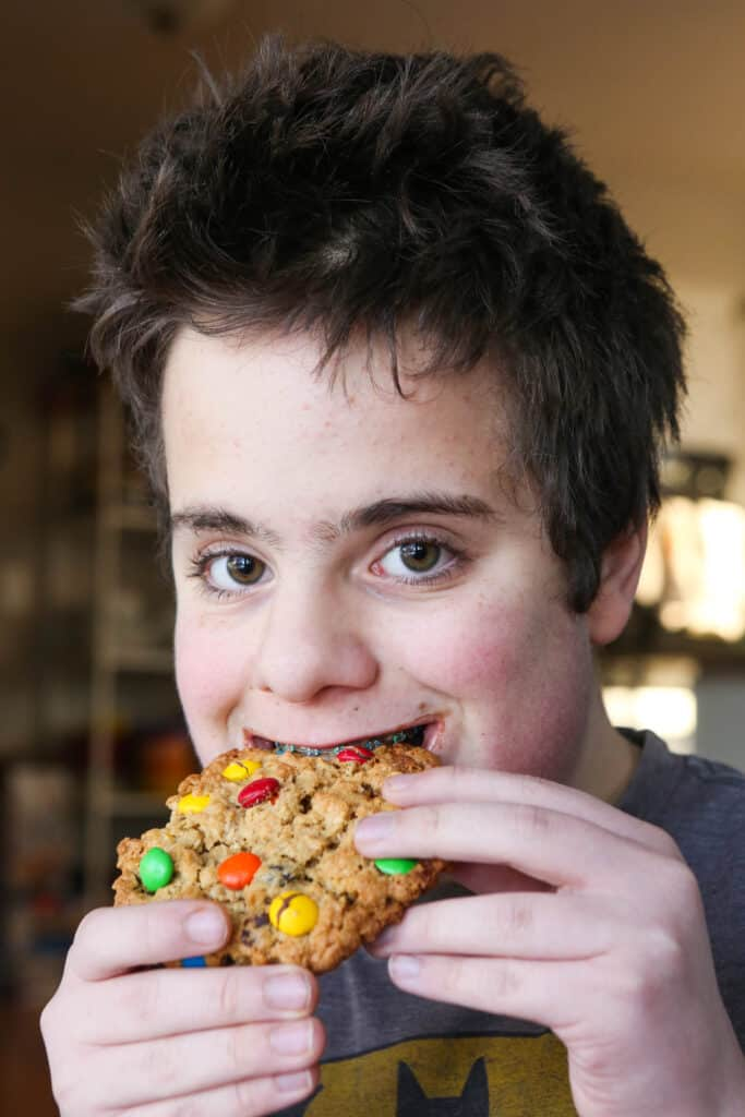 cute boy biting into a giant cookie