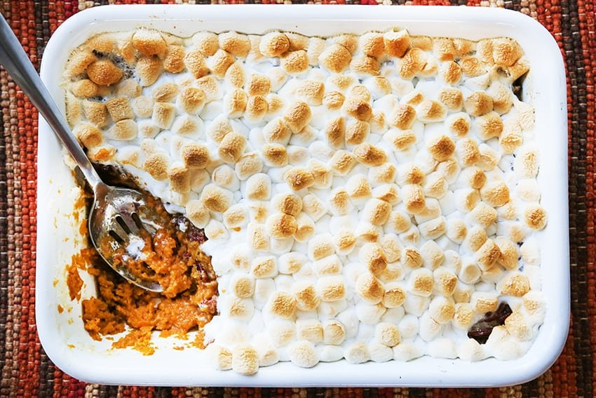 marshmallow-topped sweet potato casserole with serving spoon inside