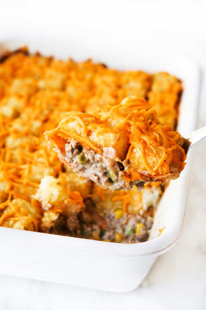 spoonful of tater tot hotdish being removed from baking pan