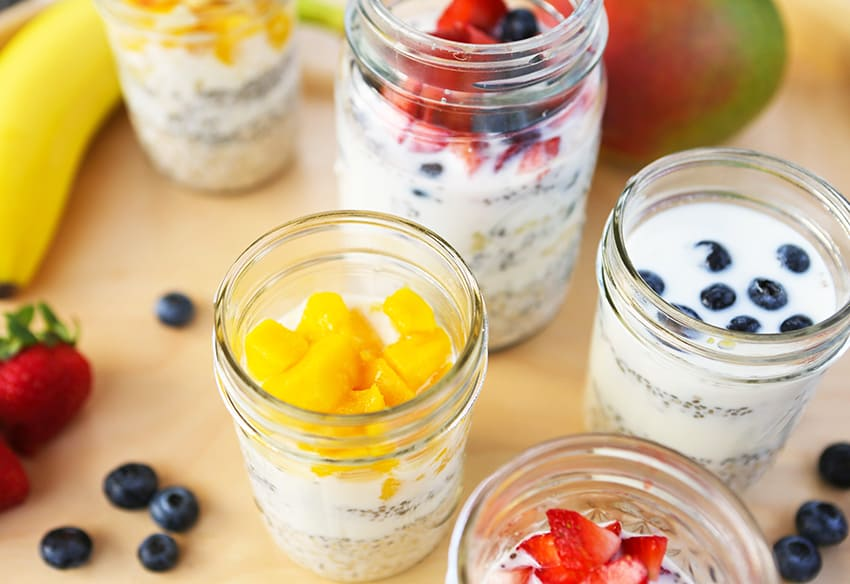 mason jars in a line filled with overnight oatmeal ingredients