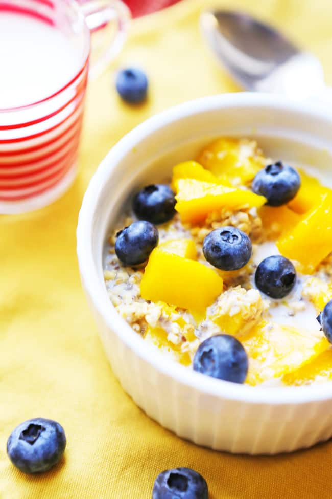 serving of overnight oatmeal in a small bowl with blueberries and peaches