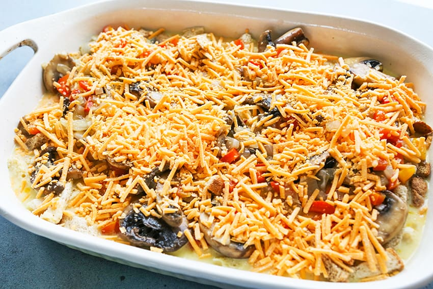 shredded cheese over the top of other casserole ingredients in a baking dish