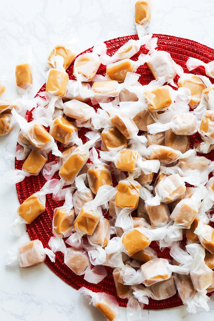 wrapped homemade caramels on a red placemat