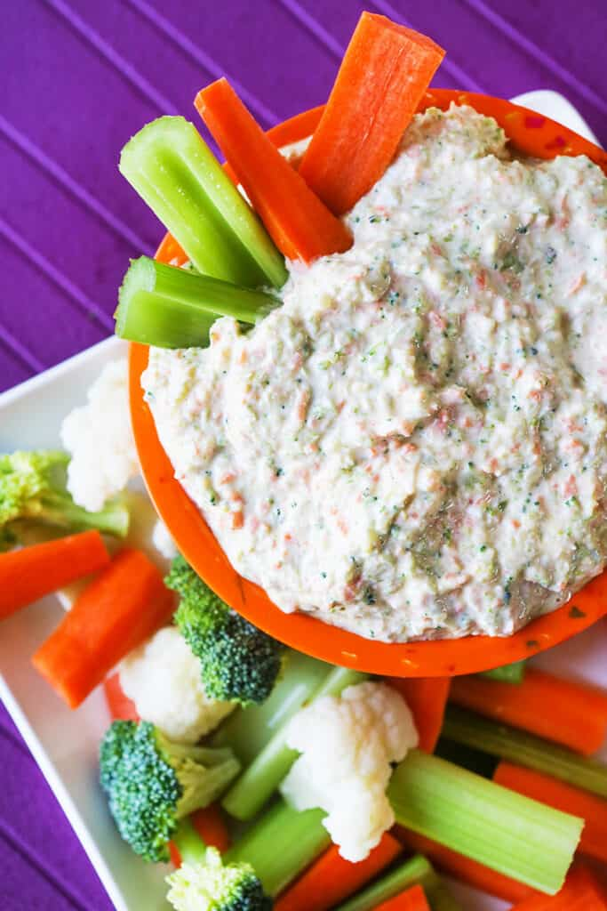 top view of creamy veggie dip with carrots and celery sticks sticking out of it