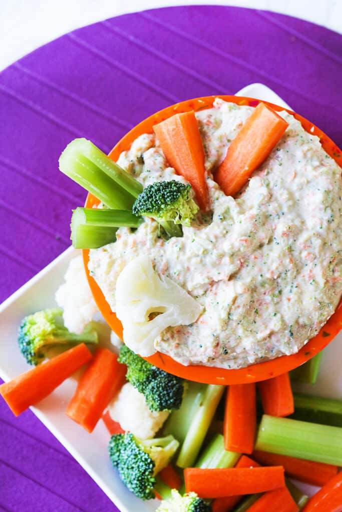 top view of cold vegetable dip surrounded by chopped fresh veggies