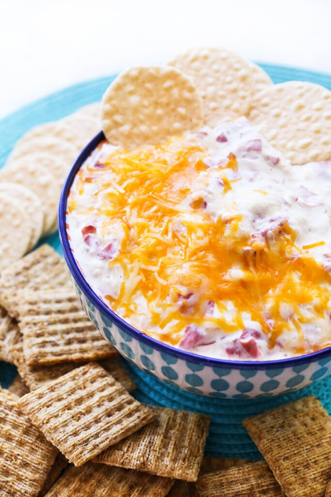gooey cheesy dip in a bowl with crackers, ready to be eaten