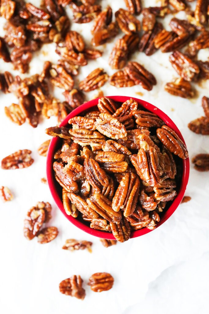 top view of a bowl of sugared pecans with others on parchment below