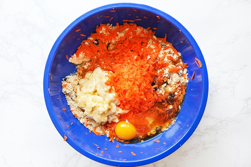 Mixing bowl with shredded carrots, mashed bananas and an egg sitting on top