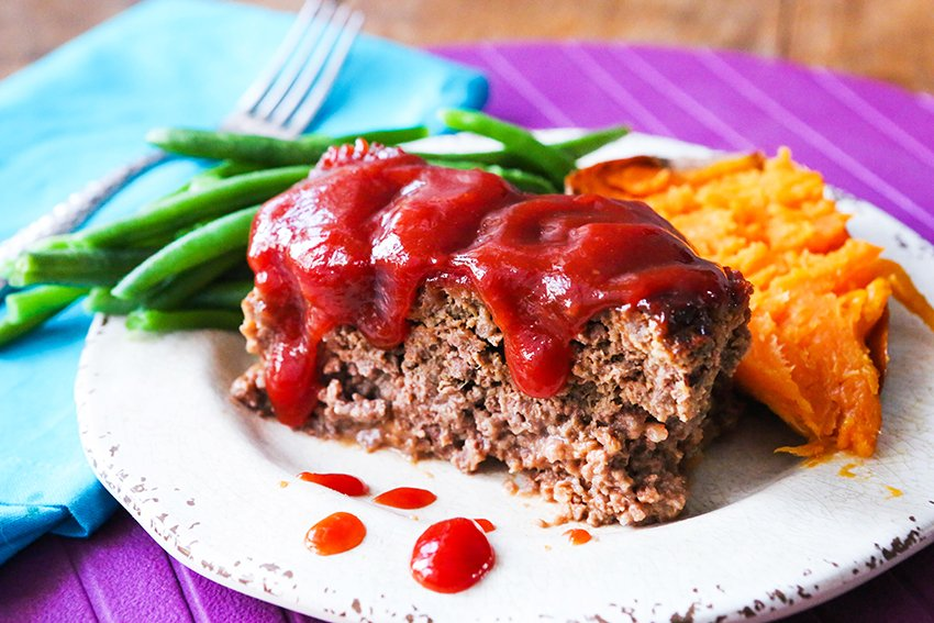 serving of meatloaf on a plate with a sweet potato and green beans