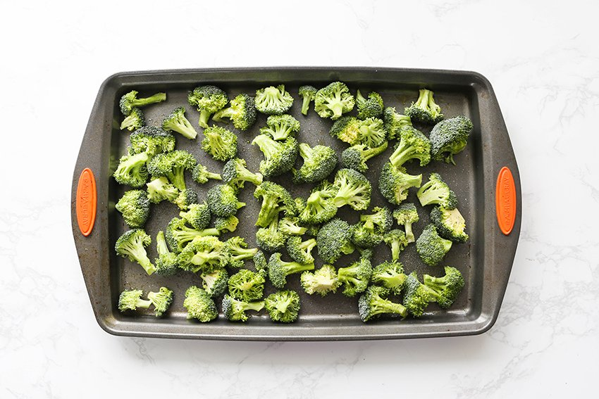 top view of a baking sheet filled with broccoli florets