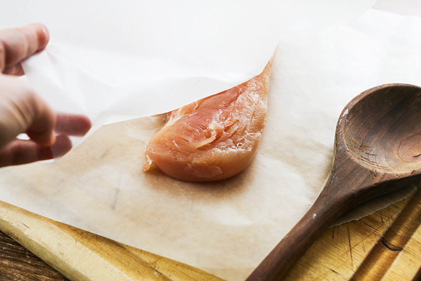 pounded chicken breast between two pieces of wax paper