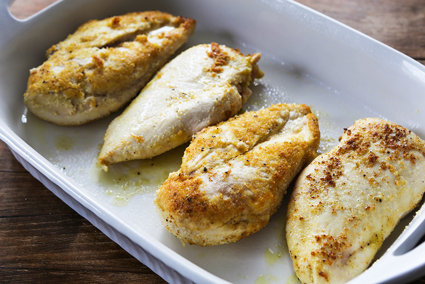 chicken breasts lined up in a baking dish before baking lemon chicken piccata