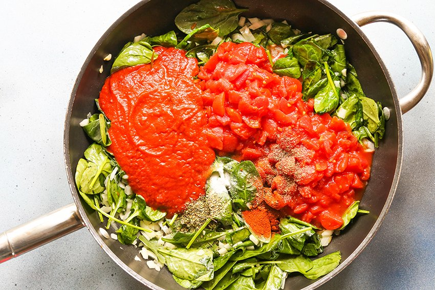 marinara, tomatoes, spinach and other ingredients in a skillet