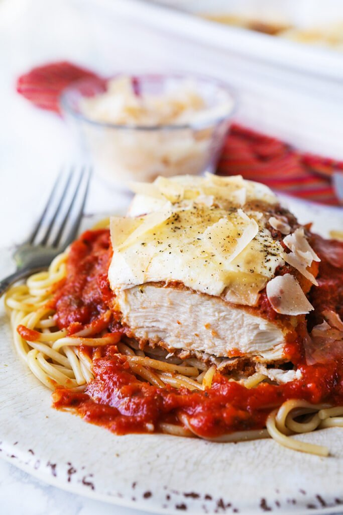 piece cut out of easy chicken parmesan over top a pile of spaghetti noodles