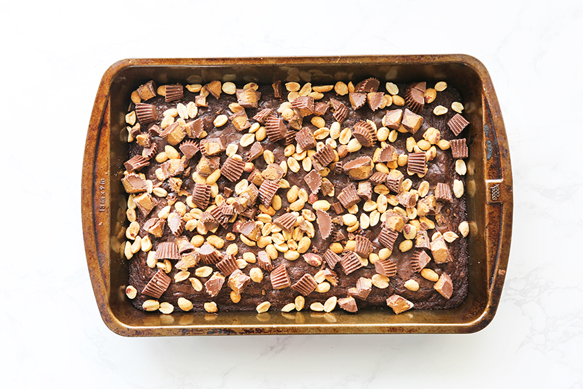 pan of brownies topped with a layer of peanuts and Reese's peanut butter cups