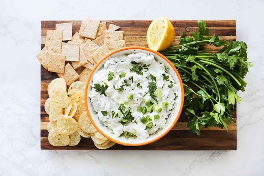 feta dip on a cutting board with crackers, chips and parsley