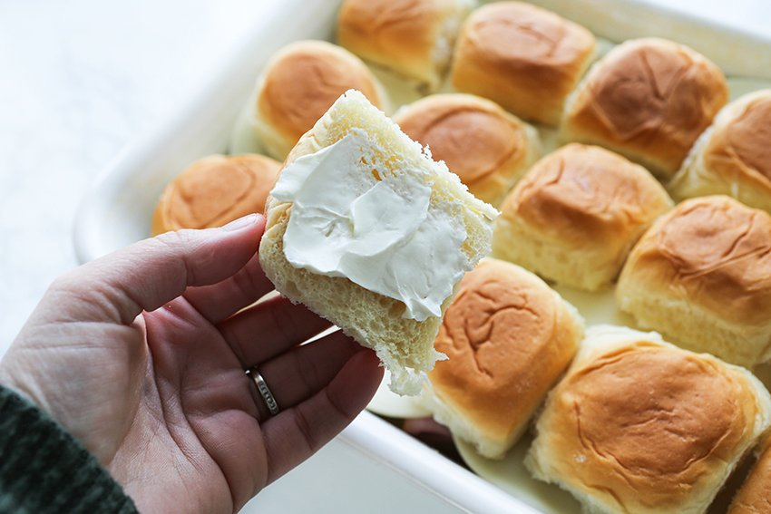 cream cheese spread onto the bottom side of a roll