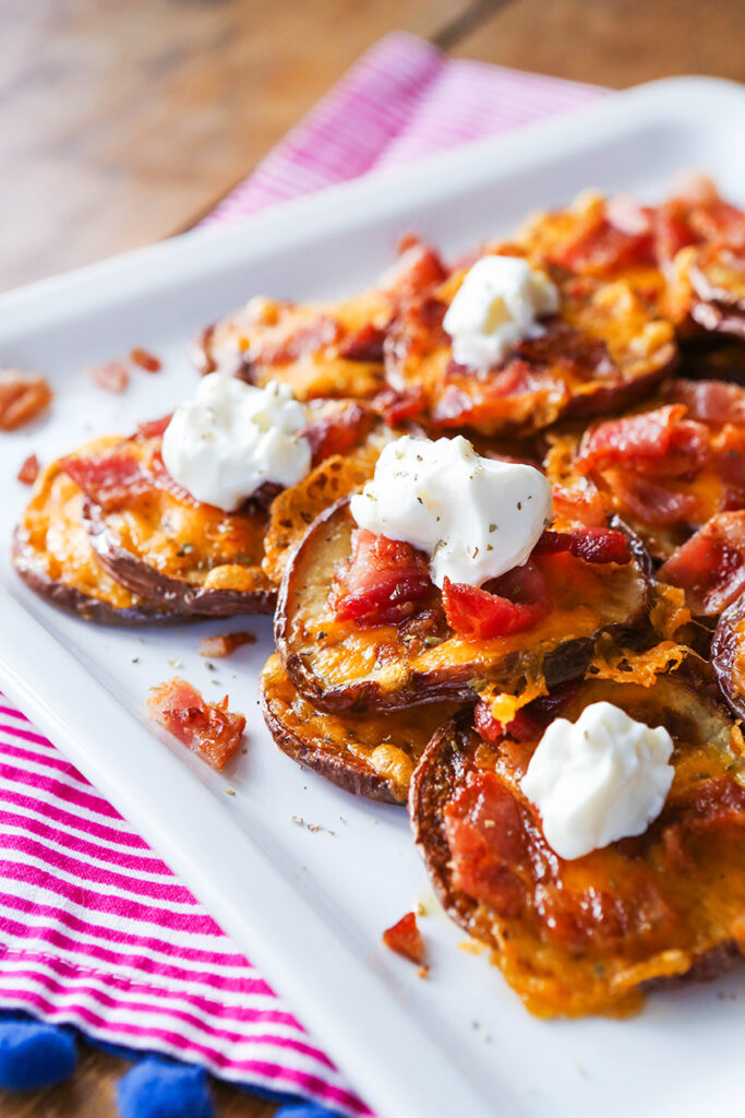 loaded baked potato rounds on serving plate topped with sour cream