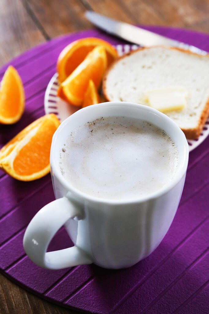 skinny latte recipe in a mug sitting next to toast and orange slices