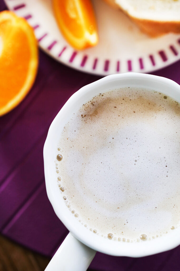 top view of a mug with a skinny latte inside, sitting next to orange slices