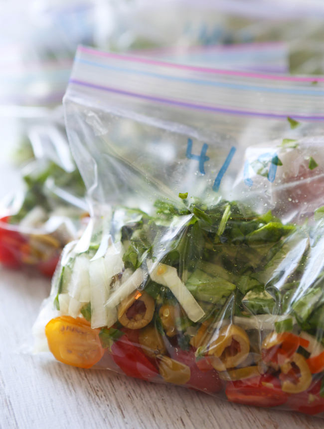 ziploc bags filled with tomatoes, olives, onions and spinach