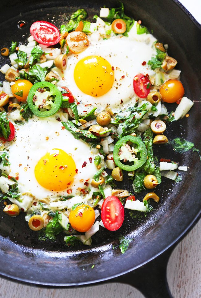 looking down into a skillet with over easy eggs and vegetables surrounding them
