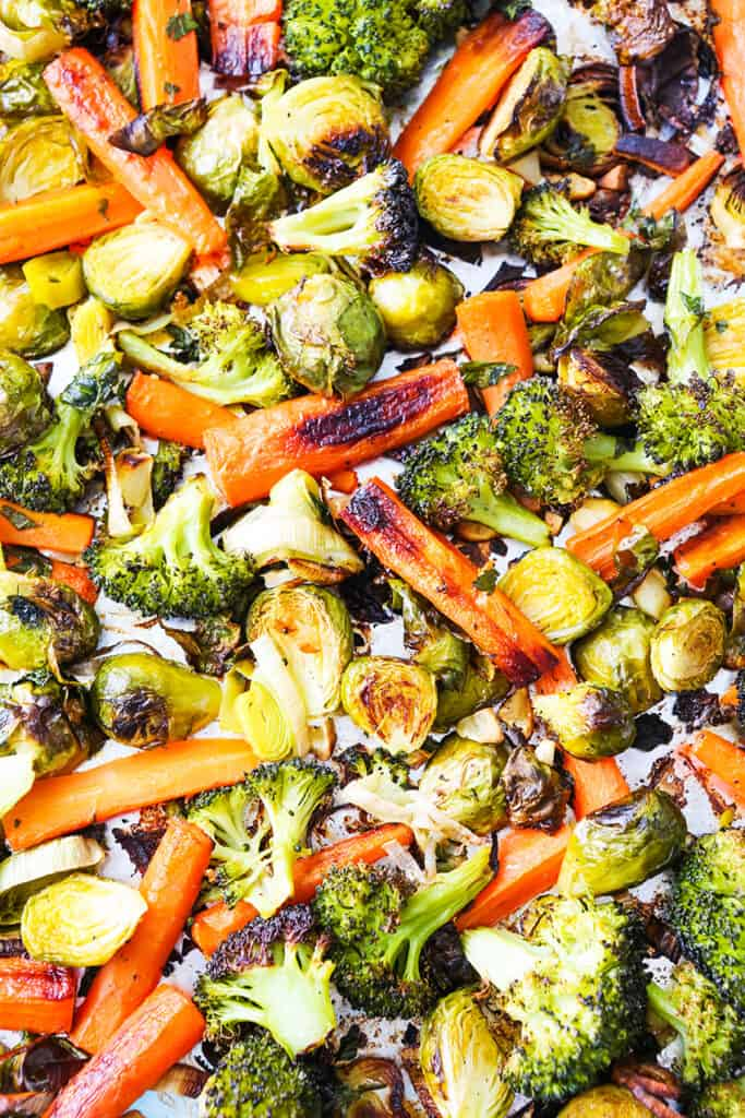 baking sheet filled with roasted vegetables: carrots, broccoli, brussels