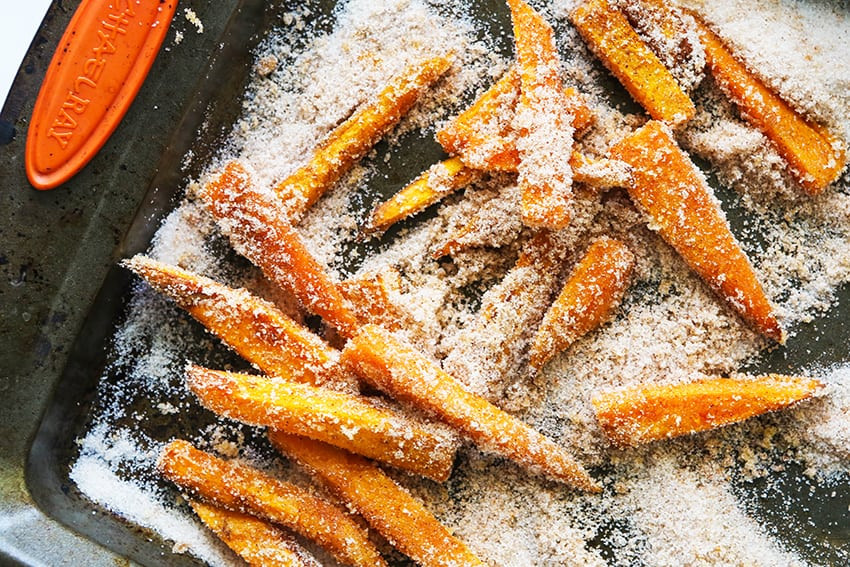 sweet potato fries doused in sugar on a baking sheet