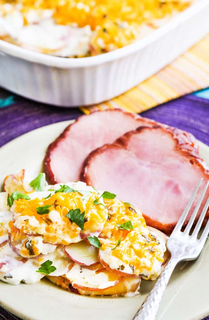 plated ham and scalloped potatoes next to a baking dish
