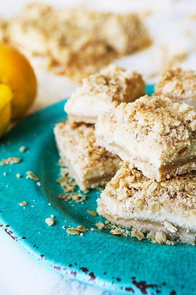 lemon crumble bars stacked on a teal plate, sitting next to 2 lemons