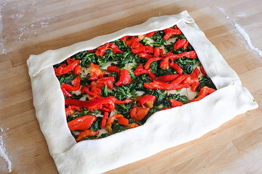stromboli calzone dough with peppers and spinach inside, ready to roll up