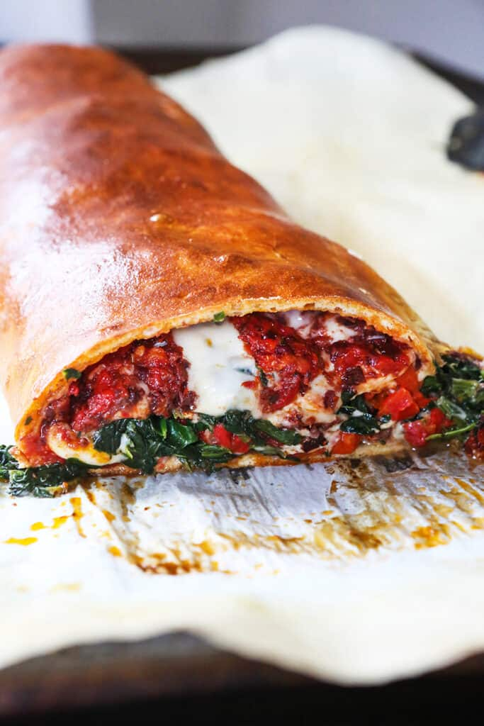 Looking into the center of a stromboli log with melted cheese, peppers and spinach oozing out