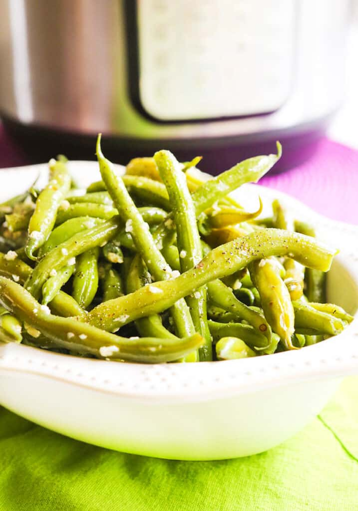 steamed green beans in serving bowl sitting next to an instant pot