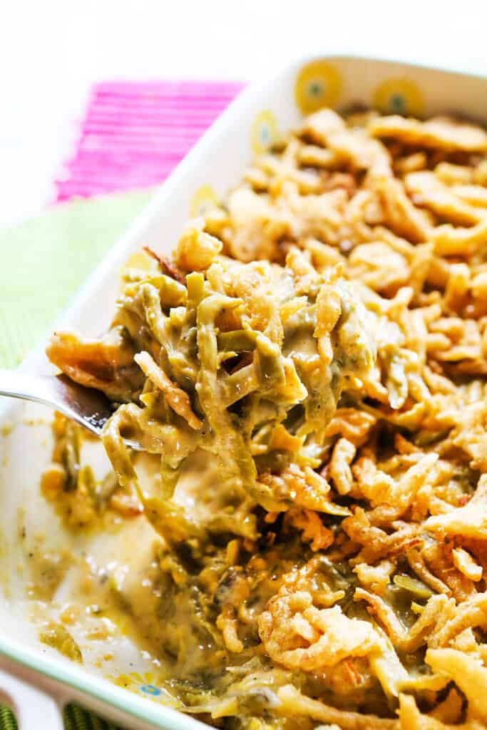 large spoonful of green bean casserole being removed from baking dish