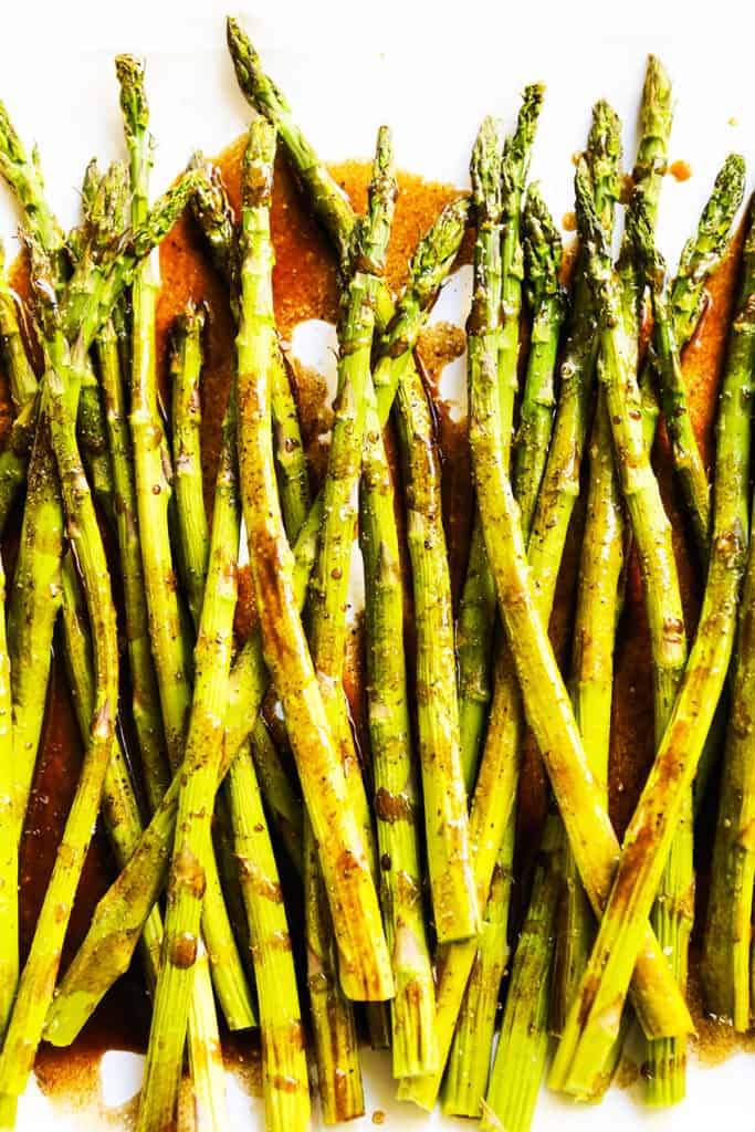 asparagus spears lined up on a white serving platter