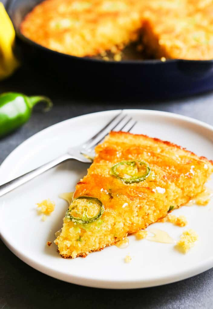 slice of cornbread on a plate with jalapeno slices on top