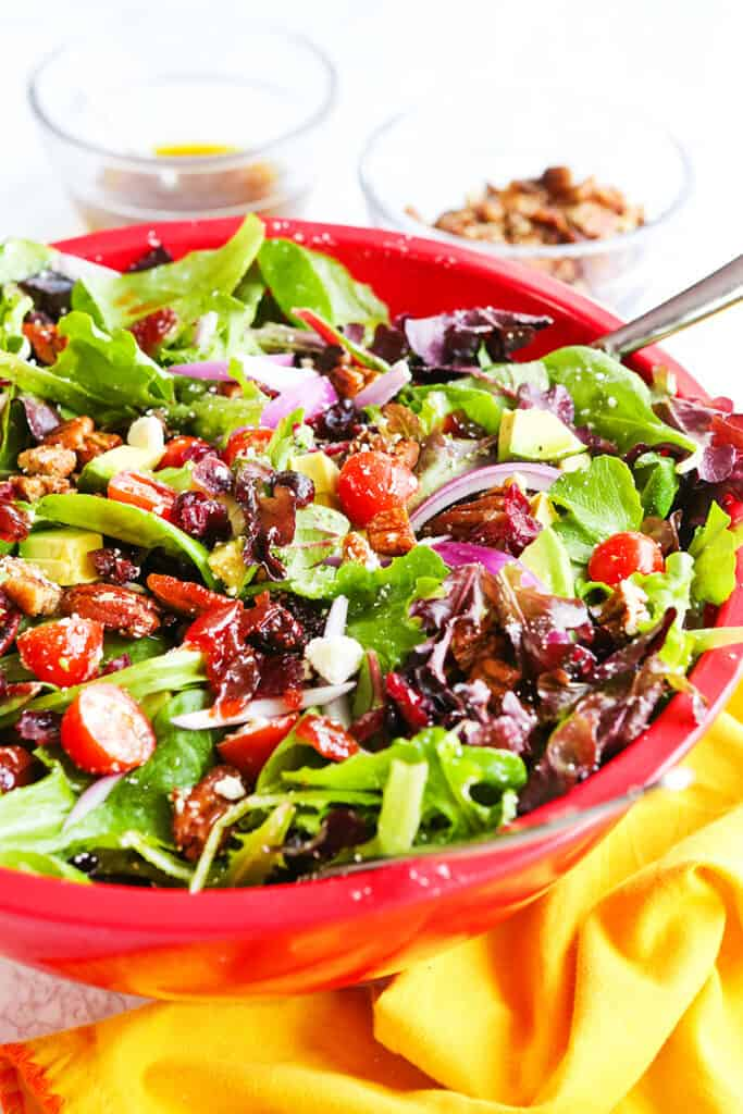 chopped salad in large red bowl packed with tomatoes, onions and pecans