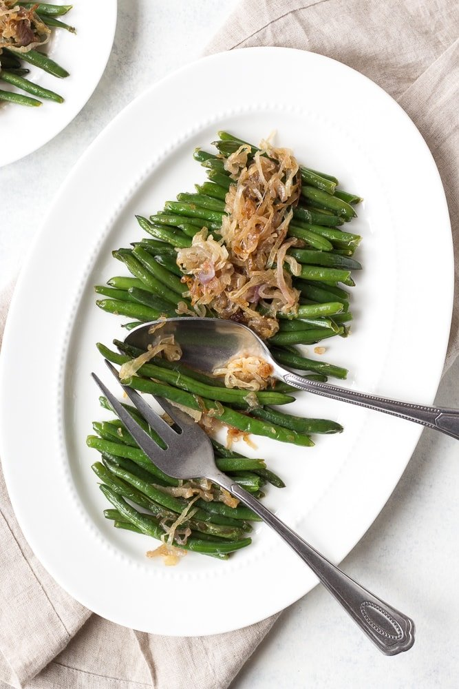 serving platter and serving forks with sauteed green beans and shallots