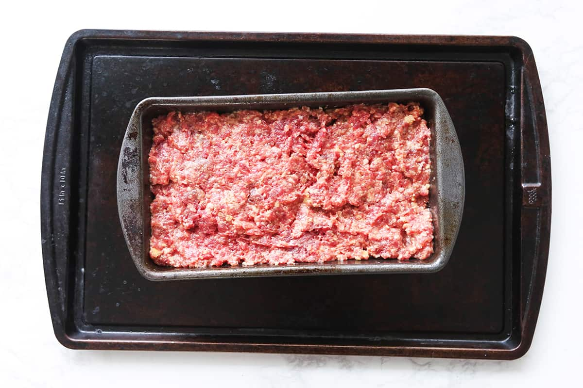 Ground beef mixture in a loaf pan.